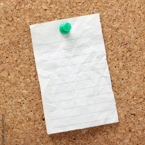 Blank piece of lined paper pinned to a cork board