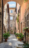 Pretty street in the ancient city of Tuscany - 57613721