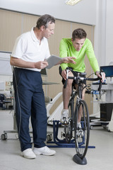Sports scientist with digital tablet monitoring cyclist on exercise bike in laboratory