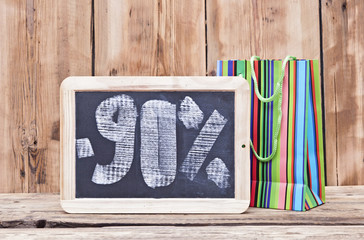 ninety percent discount written on blackboard with colorful shop