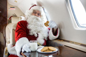 Santa Having Cookies And Milk In Private Jet
