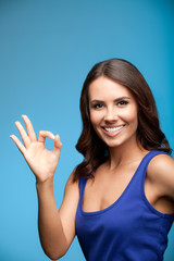 Woman showing okay gesture, over blue