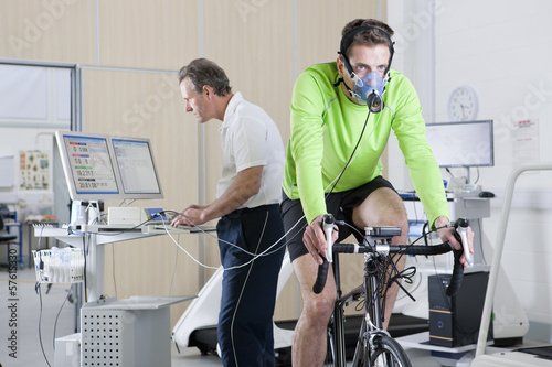 Sports scientist at computer and cyclist with mask on exercise bike in laboratory
