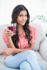 Pleased cute brunette sitting on couch holding glass of juice