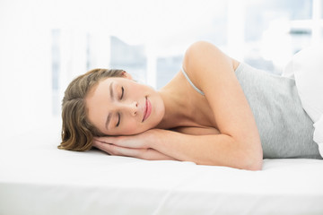 Calm sleeping woman lying in her bed