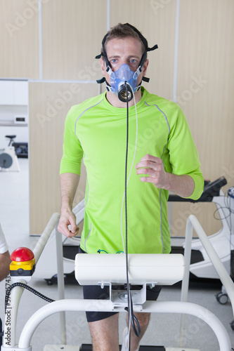 Portrait of runner wearing mask on treadmill in sports science laboratory