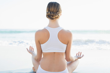Rear view of calm young woman meditating