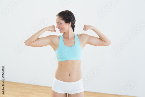 Fit young woman flexing muscles