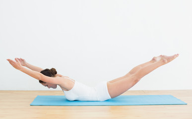 Side view of a woman exercising on mat