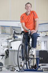 Portrait of confident cyclist on exercise bike in sports science laboratory