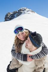 Man piggybacking cheerful woman against snowed hill
