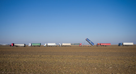 Row of trucks working on field