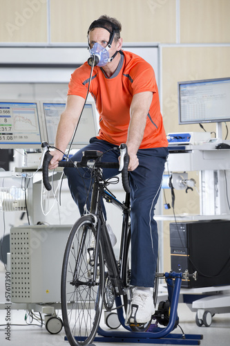 Cyclist wearing mask on exercise bike in sports science laboratory