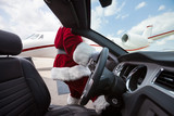 Santa Driving Convertible At Airport Terminal
