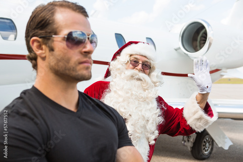 Santa Waving Hand With Bodyguard In Foreground Against Private J