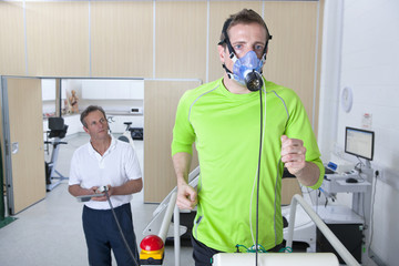 Sports scientist monitoring runner with mask on treadmill in laboratory