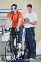 Sports scientist with digital tablet monitoring cyclist with mask on exercise bike in laboratory