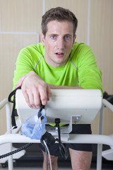 Portrait of serious runner holding mask and leaning on treadmill in sports science laboratory