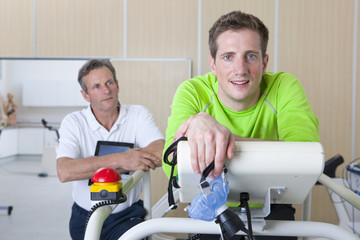 Portrait of runner holding mask and leaning on treadmill in laboratory with sports scientist in background