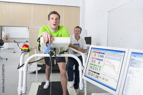Sports scientist monitoring runner holding mask on treadmill in laboratory