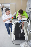 Sports scientist talking to runner with mask on treadmill in laboratory
