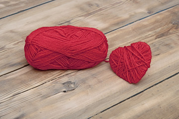 Knitted heart and red of yarn on wood background