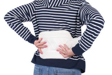 Frau mit Wärmflasche bei Rückenschmerzen
