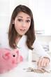 Junge Frau im Büro mit Sparschwein und Geld - Konzept