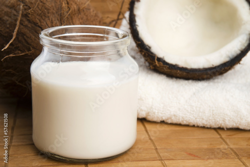 coconut fruit with a jar filled with coco milk