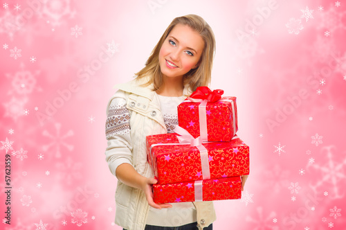 Young girl with gift boxes on winter background