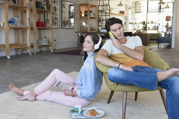 Couple using cell phone, headphones and digital tablet in livingroom