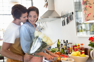 Man surprising woman in kitchen with bouquet of flowers