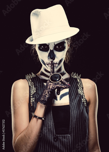 Woman with skeleton face art making a hush gesture