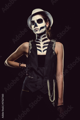 Woman with skeleton face art over black background