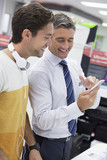 Salesman showing man cell phone in electronics store