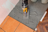 Home renovation worker trowel spreading mortar for ceramic tile