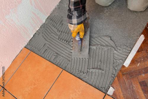 Home renovation worker trowel spreading mortar for ceramic tile