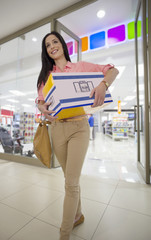 Smiling woman leaving electronics store with boxed speakers