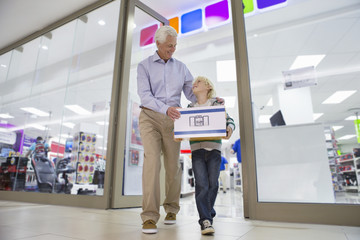 Grandfather and grandson leaving electronics store with boxed speakers