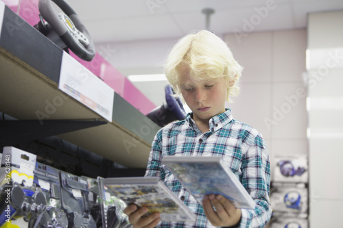 Boy looking at video games in electronics store