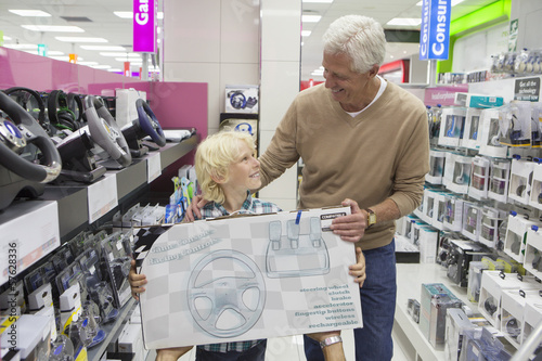Smiling grandfather and grandson holding video game box in electronics store