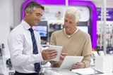 Smiling salesman showing senior man digital tablets in electronics store