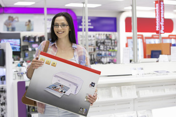 Portrait of smiling woman holding printer box in electronics store