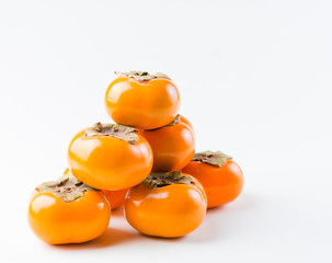 Fresh, delicious, organic Fuyu Persimmon on white background
