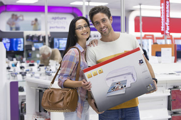 Portrait of smiling couple holding printer box in electronics store