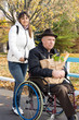 Smiling woman helping her disabled father