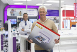 Portrait of smiling senior man holding printer box in electronics store