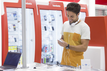 Smiling man looking at cell phone in electronics store