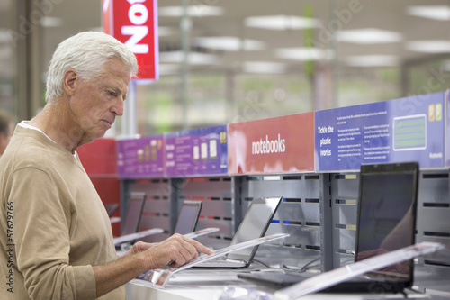 Senior man looking at prices on laptops in electronics store
