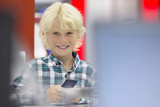 Portrait of smiling boy looking at cell phone in electronics store